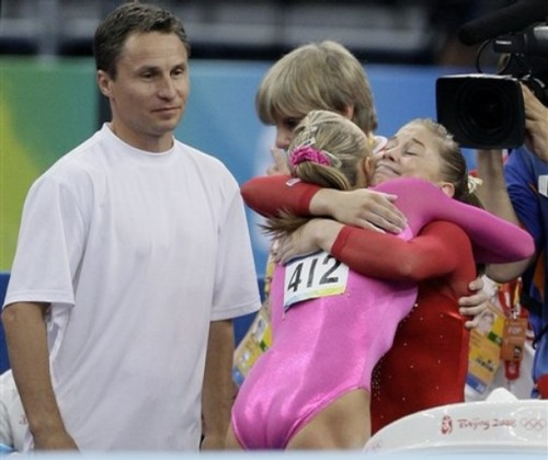 Shawn Johnson (R) & Nastia Liukin embrace as Valeri Liukin looks on